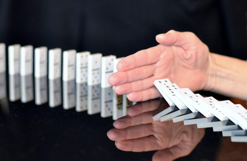 hand stopping dominoes